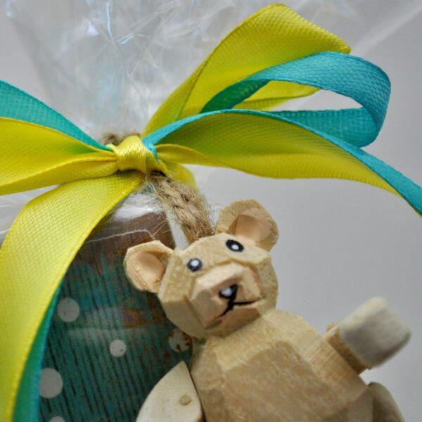 Foto van een detail van de verpakking, is een klein houten beertje aan een touwtje.